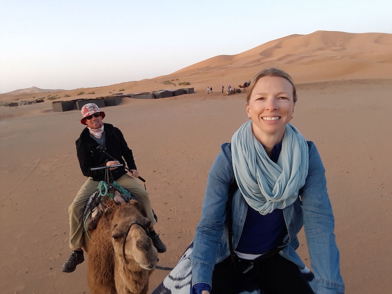 Man and woman riding camels through the Sahara Desert at Merzouga, Morocco.