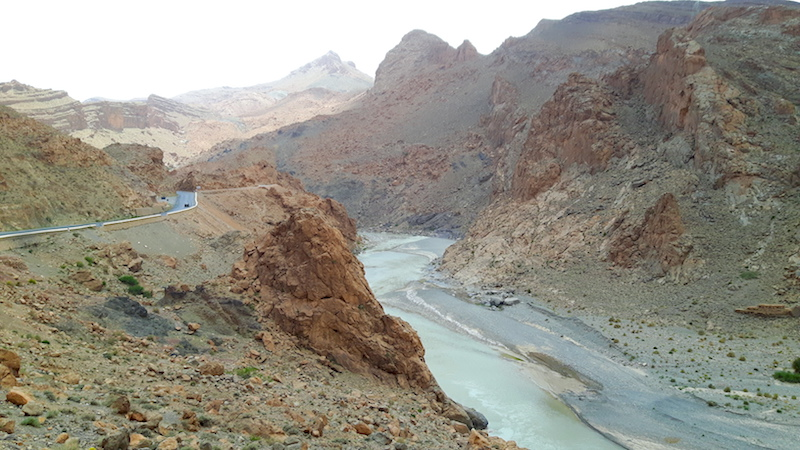 Rugged, rocky scenery with a river running through a valley and a road following it through the Atlas Mountains in Morocco.