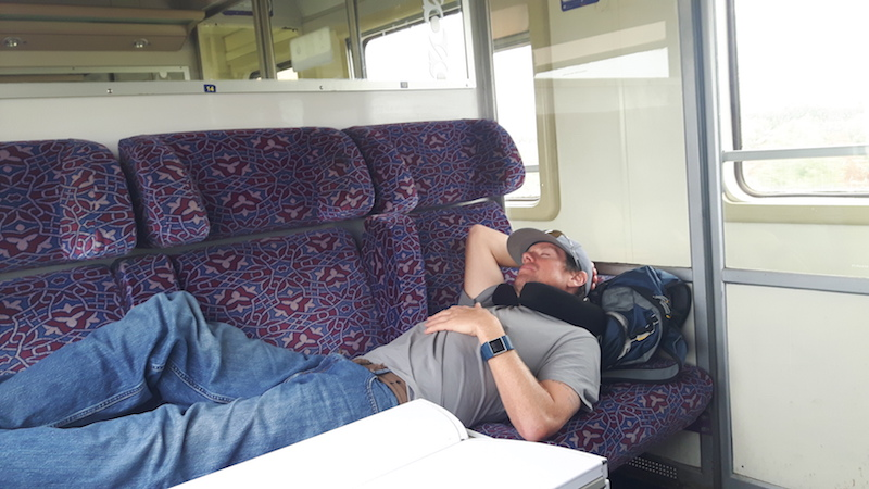 Man laying across three seats sleeping in a train in Morocco.