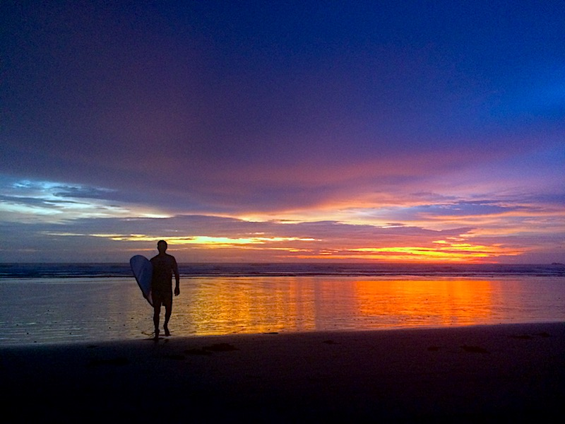 Brilliant oranges, purples and blues at sunset with the silhouette of a man carrying a surfboard out of the water in Nosara, Costa Rica.