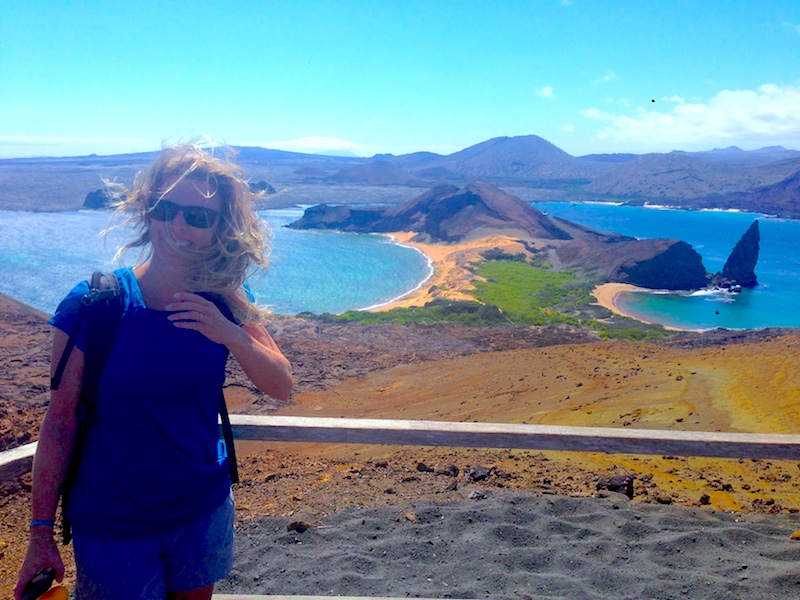 Woman at a lookout for pinnacle rock on Isla Bartolome with windswept hair in the Galapagos Islands.