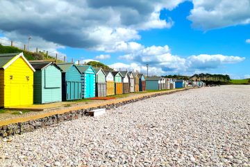 Colourful beach huts on a pebble beach. Devon, England