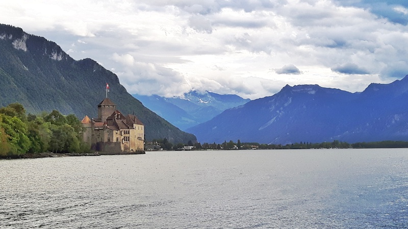A European style castle on the edge of Lake Geneva with the Alps mountains all around. Chateau Chillon in Montreax, Switzerland.