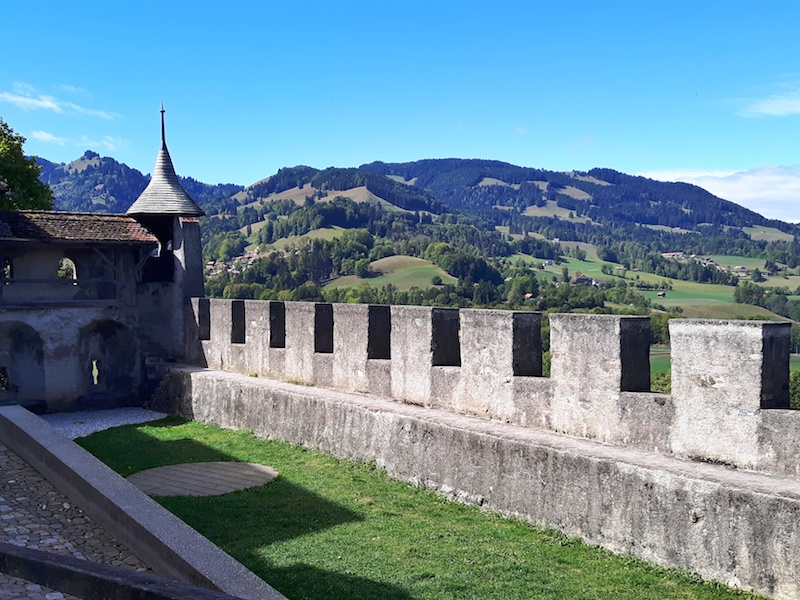 Turreted stone wall with tower at the end in Gruyere overlooking the green hillside, in Switzerland.