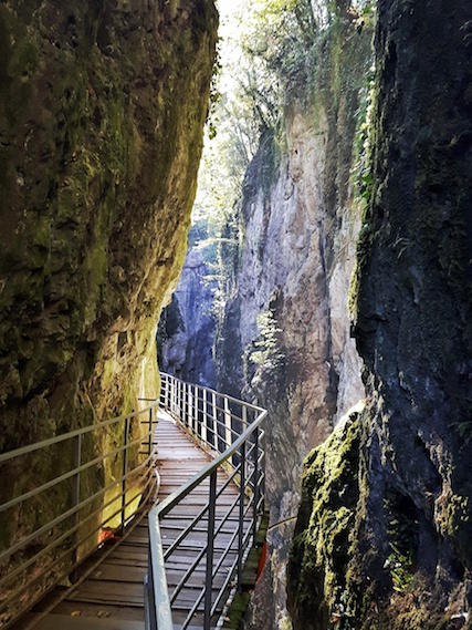 Suspended walkway through a tall, narrow Gorges du Fier, Annecy France.