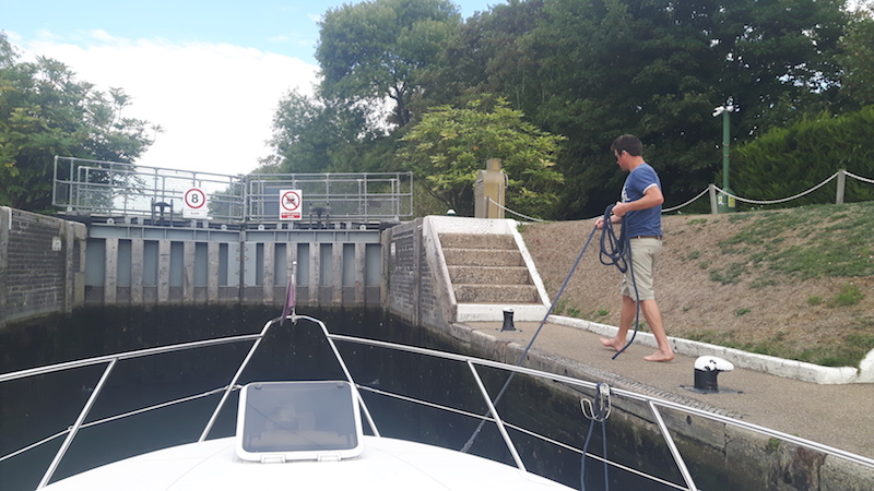 Man holding rope to guide boat through lock gates on River Thames, England.