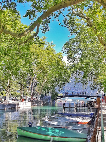 Row of canal boats with a bridge over entrance to Lake Annecy, surrounded by French Alps.
