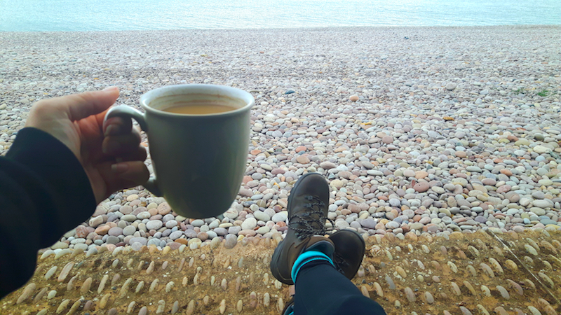 Hiking boots and a coffee on a pebble beach in Budleigh Salterton, Devon England.
