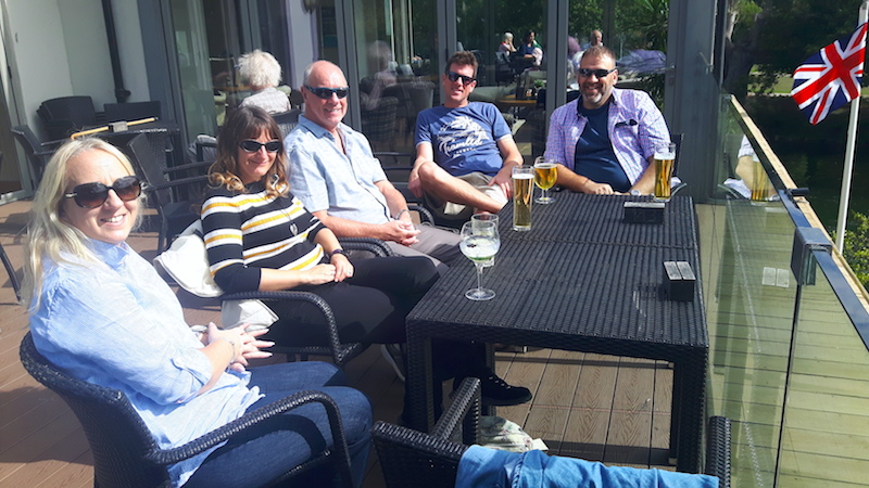 Five adults having a drink on a patio overlooking the River Thames in Maidenhead, UK.