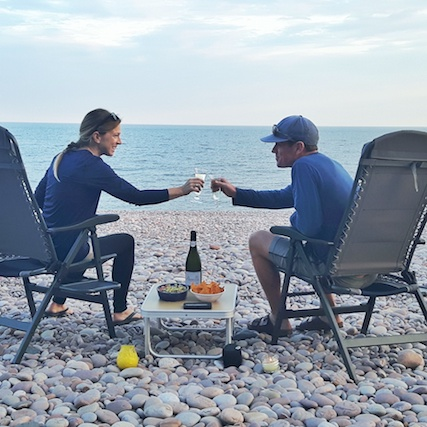 Man and woman with a drink and snacks on a pebble beach in Budleigh Salterton, Devon UK.