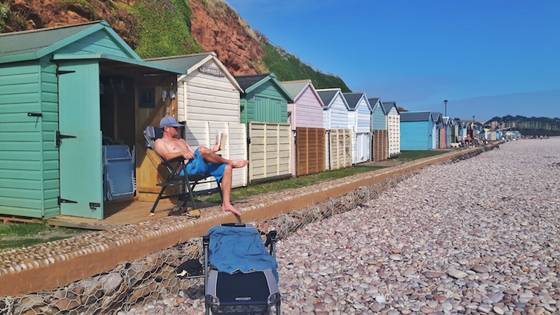 Man reading outside an open beach hut in a row of beach huts on the pebble beach in Budleigh Salterton, Devon England.