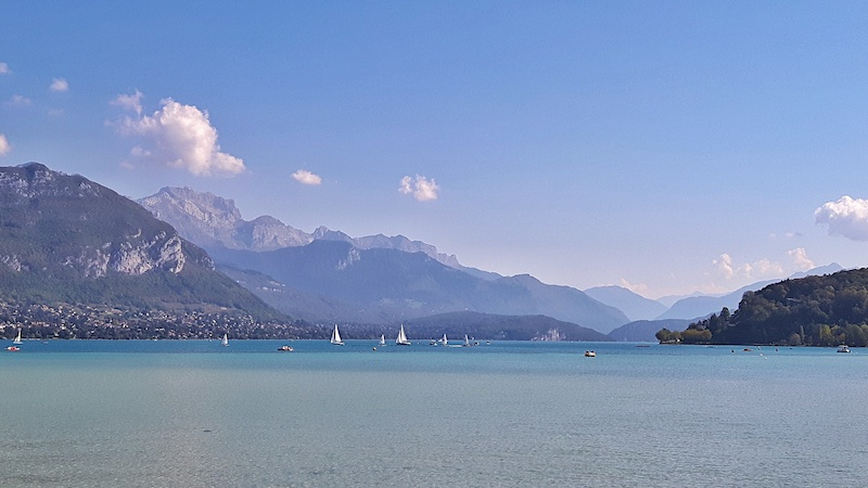 Sail boats in the turquoise waters of Lake Annecy backed by the Alps, France.