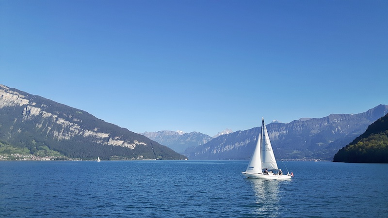 White sails of a yacht in Lake Thun, surrounded by the Swiss Alps, Switzerland.