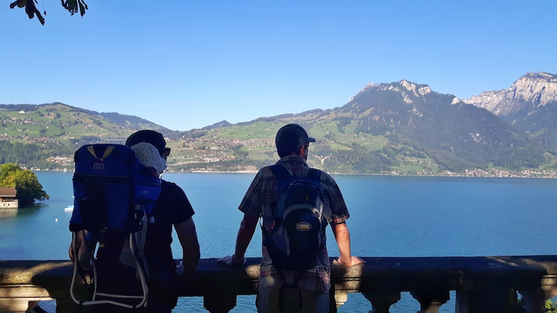 Two men and a baby, view Lake Thun, Switzerland.