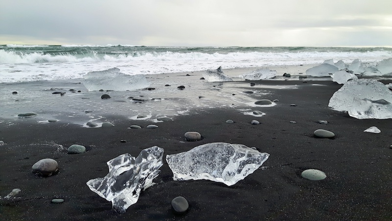 Chunks of clear ice on a black sand beach on the south coast of Iceland.