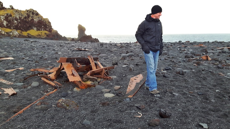 Man walking among rusted metal pieces from a shipwreck on Djupalonssandur black sand beach, Iceland.