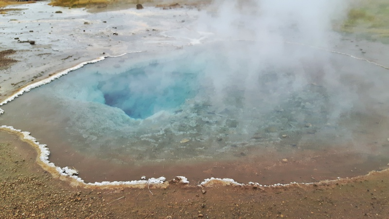 Clear blue water steaming in a geyser on the golden circle in Iceland.