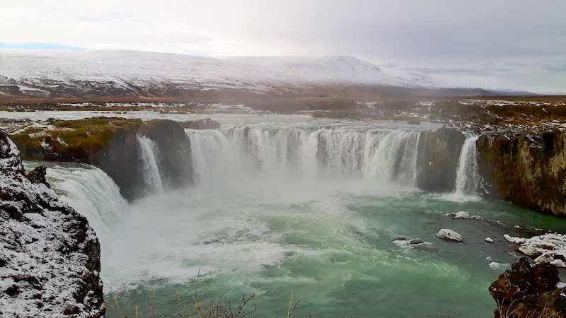 Large horseshoe shaped waterfall crashing into emerald waters at Godafoss Waterfall, Iceland.