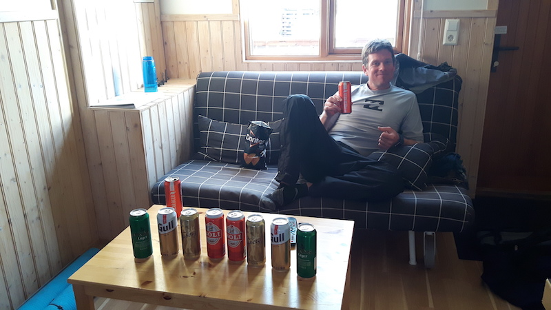 Man sitting on a couch with a row of Icelandic beer cans on the table.