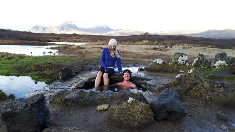 Man in a hole in the ground with a woman sitting on the edge of a hot pot in a field in Iceland.
