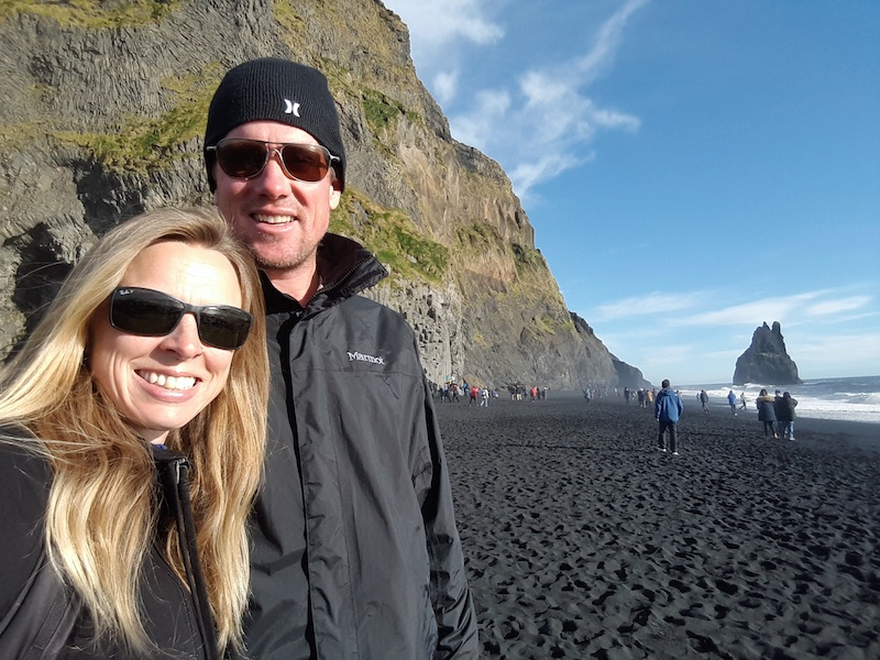 Man and woman on a black sand beach on a sunny day in Iceland.