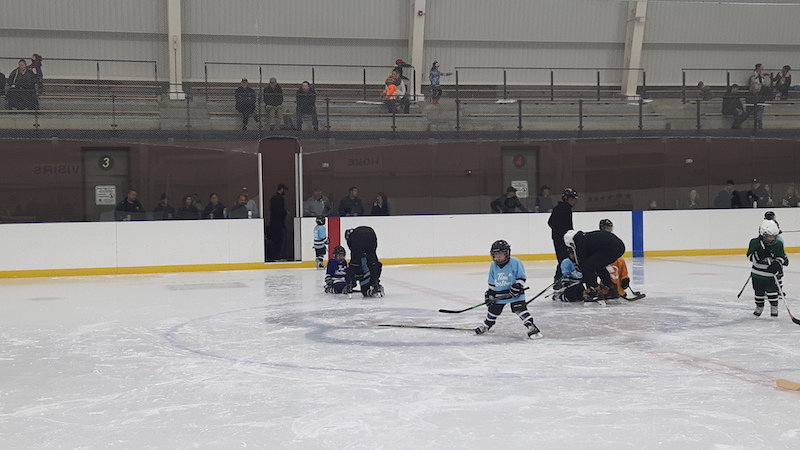 Young children playing hockey in Canada.