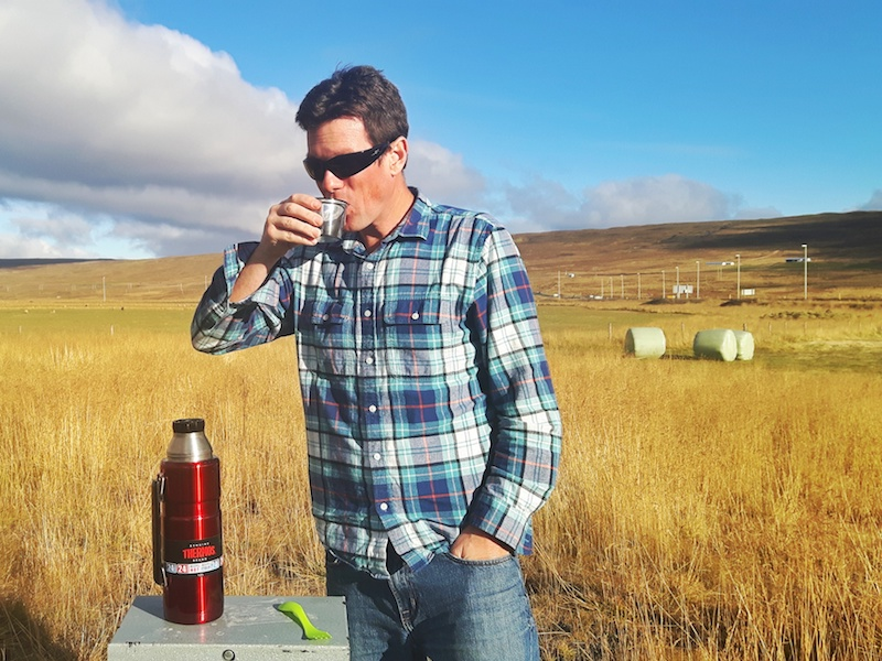 Man drinking soup from a Thermos surrounded by hay fields in Iceland.