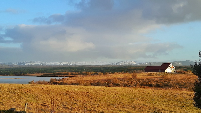 Brown grass fields lead to a lake surrounded by mountains with one lone red and white building on the shore in Iceland.