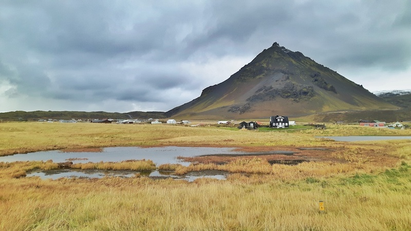 Iceland landscape, ponds, mountain, long grass and dark buildings