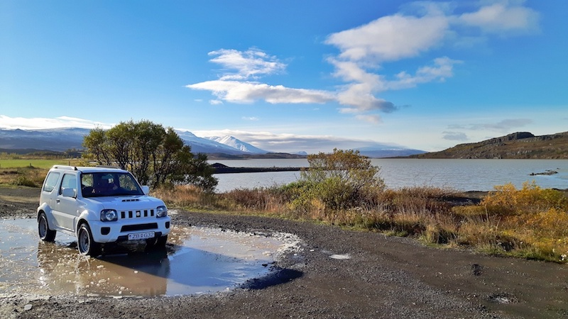 White Suzuki Jimmy car rental with lake and mountains behind - Iceland.