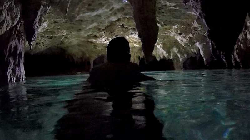 Silhouette of a man in the water in a dark cave cenote in Mexico