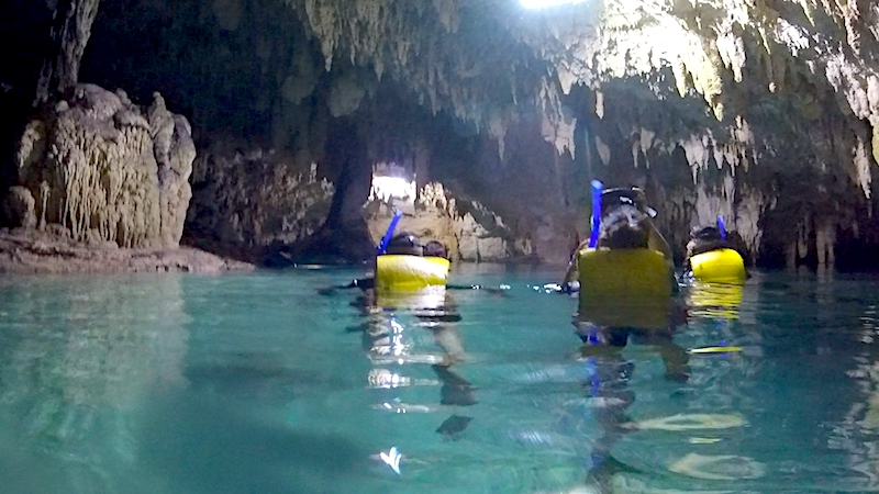 People snorkelling in Cenote Sac Actun, Mexico.