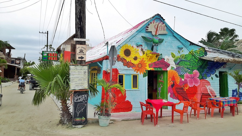 Restaurant covered in bright graffiti with plastic furniture on sandy street on Isla Holbox, Mexico