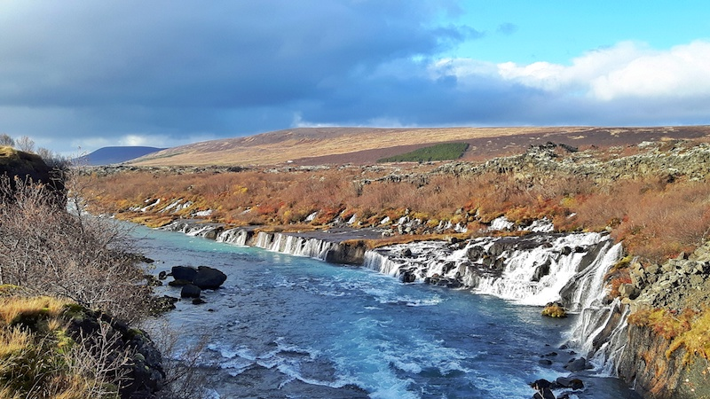 low waterfall, Hraunfossar, with water cascading through a lava field into the side of a river. Iceland.