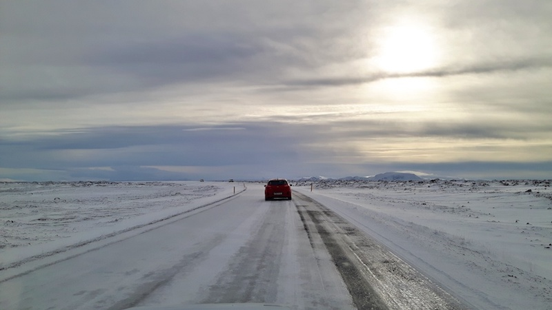 A car driving on the snow covered road to Dettifoss waterfall in Iceland