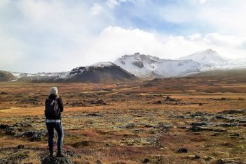 Standing on a rock looking out to snow-covered mountains across lava fields in Iceland.