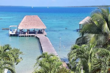 View of blue lake and palapa from our rooftop patio in Laguna Bacalar, Mexico