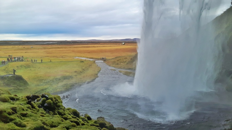 looking from behind a huge waterfall with green moss, and fall coloured fields, Seljalandsfoss, Iceland