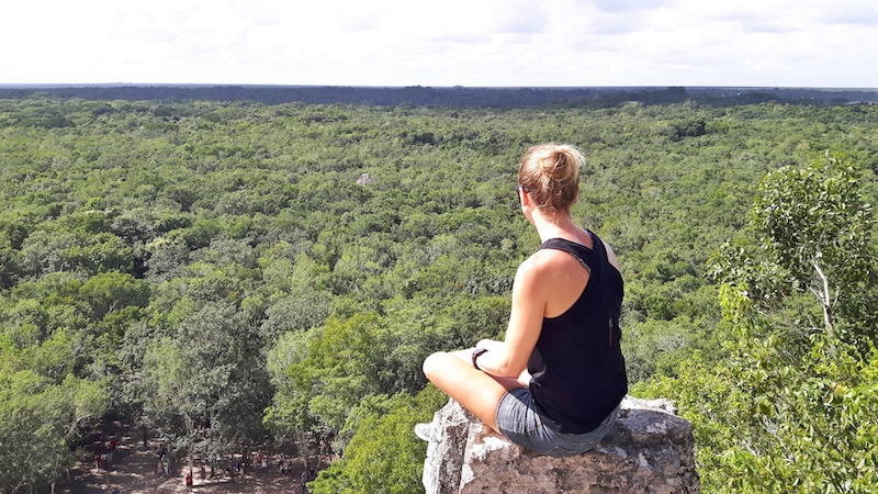 Girl sitting on top of a Maya pyramid looking over jungle at Coba, Mexico
