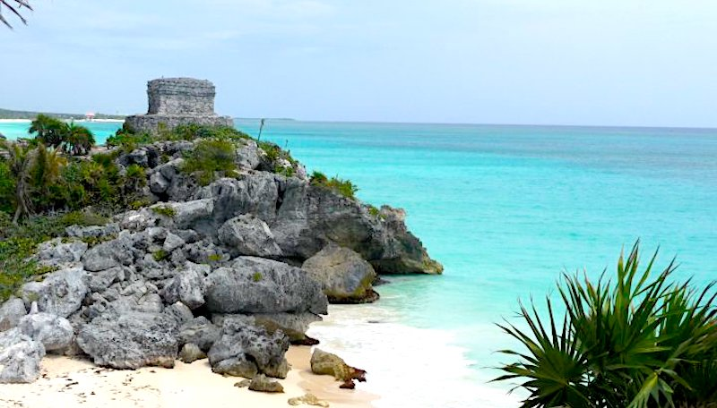 Maya ruins - watchtower on cliff overlooking turquoise Caribbean Sea in Tulum, Mexico