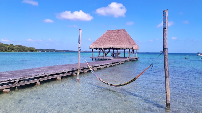 Hammock and palapa over the blue water of Laguna Bacalar in Mexico