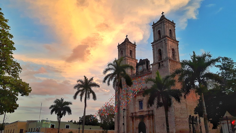 Twin towers of a cathedral with palm trees and bright sunset, Valladolid Mexico