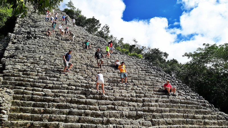 People climbing up and down the tall pyramid at Cobá, Mexico.