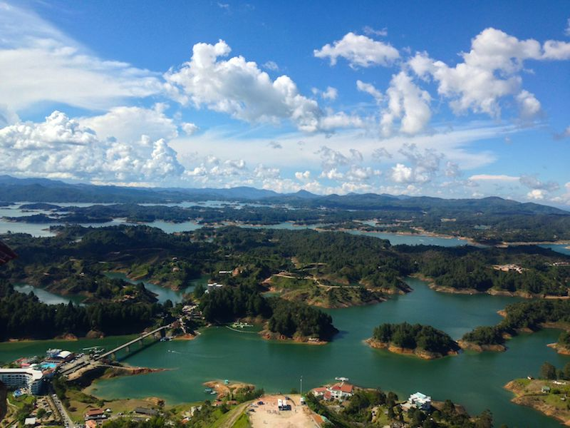 Emerald lake dotted with green islands from above in Guatape, Colombia.