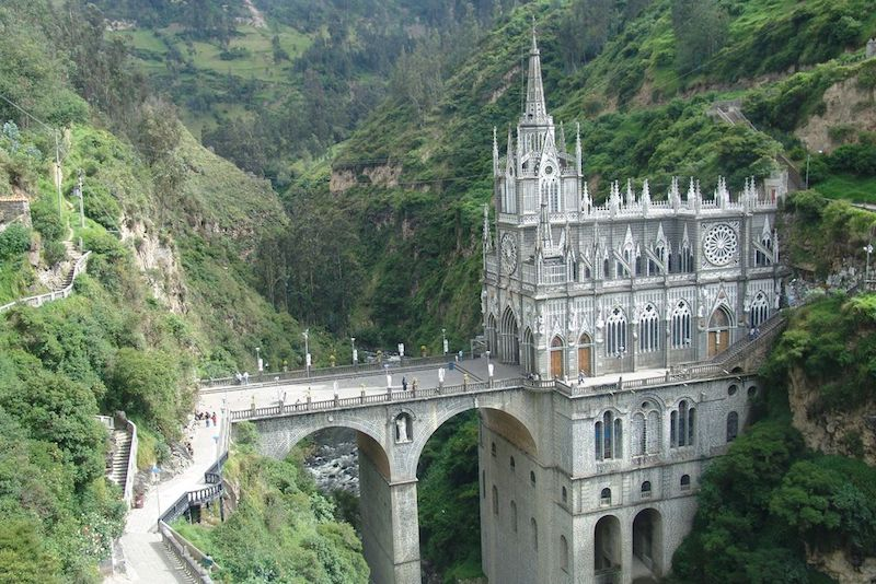 Large ornate church with very tall bridge spanning a lush green gorge in Ipiales, Colombia.