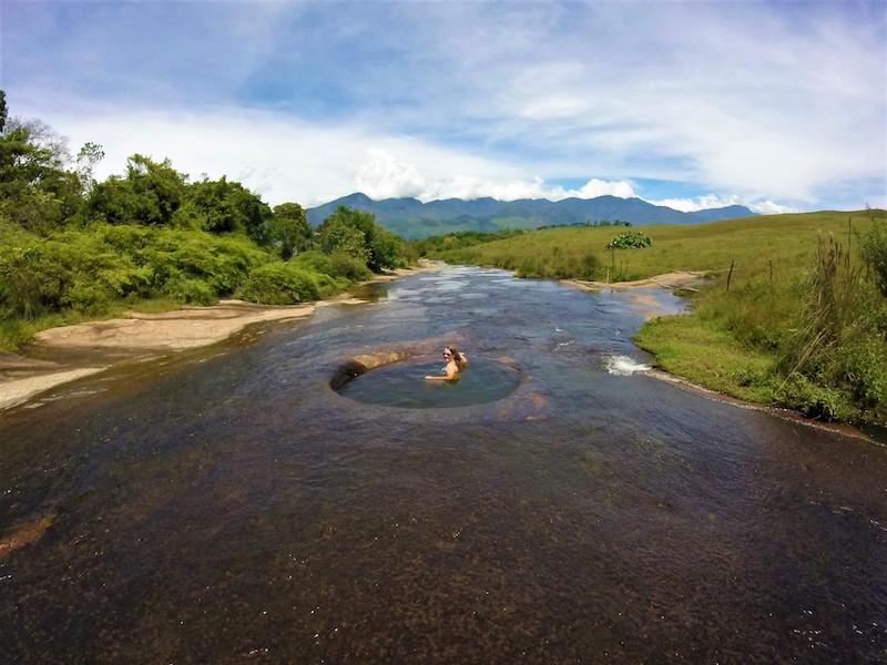 Woman sitting in a natural pool in a river surrounded by countryside and mountains in Guadalupe, Colombia.