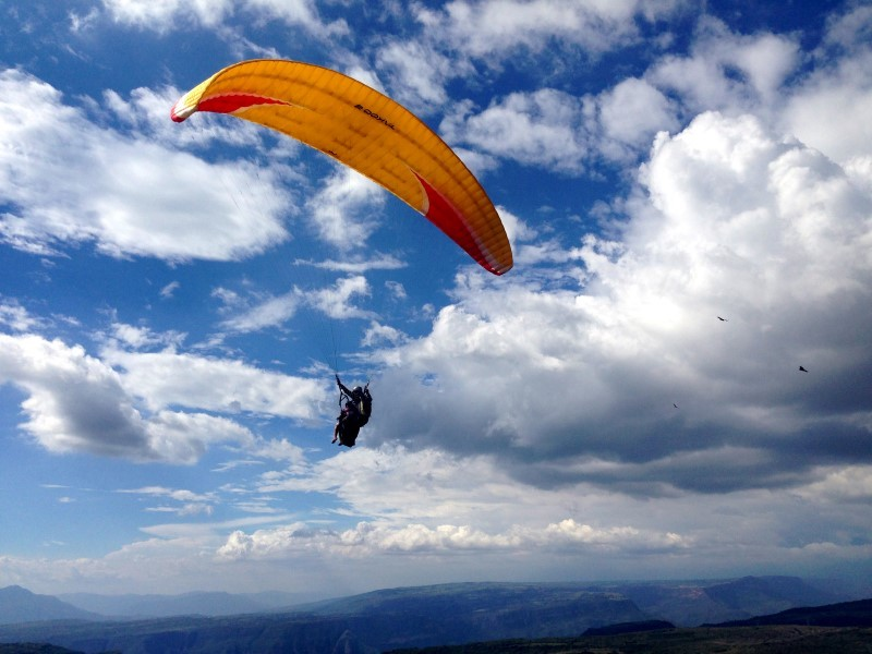 Tandem paragliding kite in the blue sky over San Gil, Colombia.