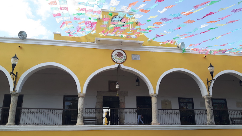 Yellow building with large arches and brightly coloured banners strung across the street in Izamal, Yucatan Mexico.