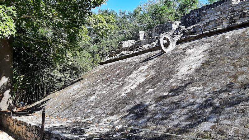 One slanted stone wall with a stone ring near the top in an ancient ball court in Coba ruin, Mexico.