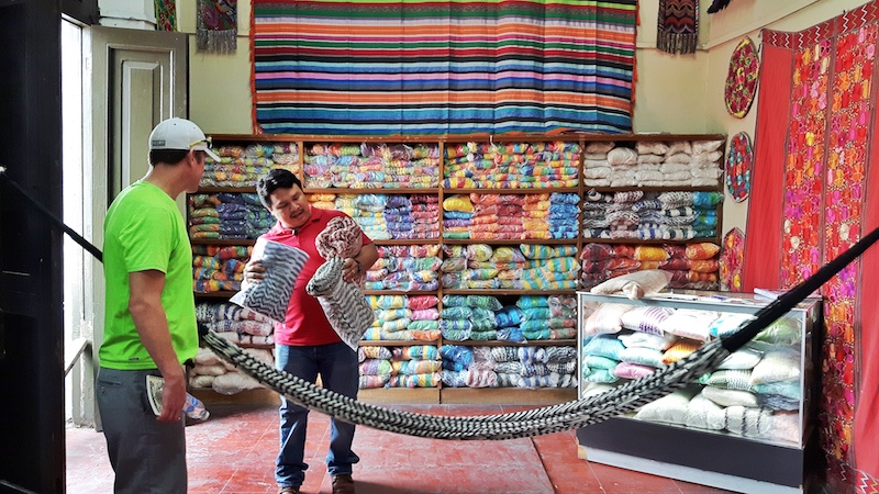 A Mayan artisan showing a man a selection of hammocks with a wall filled with bagged hammocks behind him in Merida, Mexico.